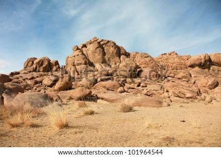 Red rocks in the barren sands of the Gobi Desert #101964544