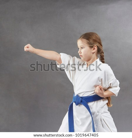 On a gray background the girl beats a blow with her hand Royalty-Free Stock Photo #1019647405