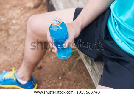 Bottle of energy drink in hands of trail runner.
