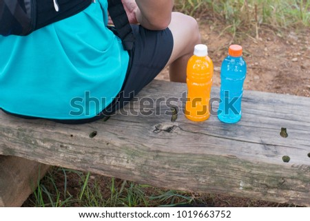 Trail runner sitting with bottle of energy drink and orange juice.
