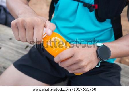 Bottle of orange juice in hands of trail runner visitor