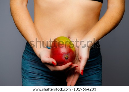 Fit Woman Holding A Mango With Mid Drift Showing On A Gray Background #1019664283