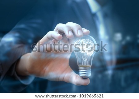 Businessman show a light bulb with a brain that light up. The concept of brainstorming and idea #1019665621