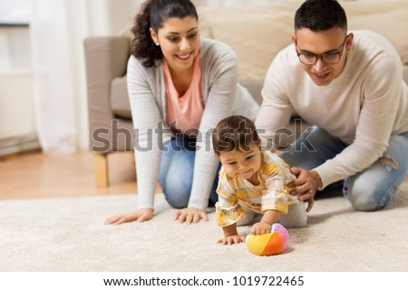 family, parenthood and people concept - happy mother, father and baby daugter playing with ball at home #1019722465