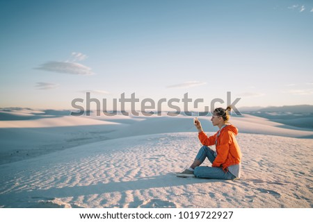 Tourist woman sitting on dunes with smartphone making picture of scenic view of desert at sunset, female tourist using telephone camera for taking photo of natural beauty of White sands scenery view