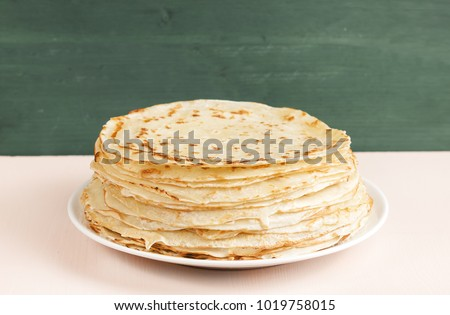 Pancakes on the white plate.  Many pancakes are stacked. Thin pancakes with crispy crust. Maslenitsa. Pancakes for breakfast and carnival. Food background. #1019758015