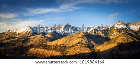 Panoramic view of a mountainside lit by a setting sun in the rocky mountains.  The glow of the sun illuminates the fall colors, along with the first snow found high up in the mountain peaks.  #1019864164