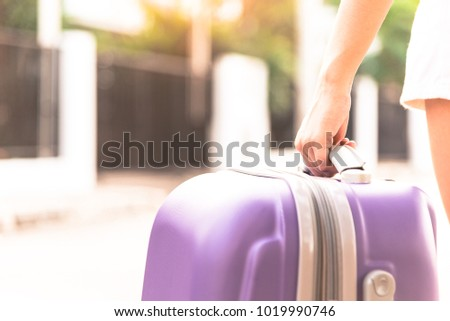 Asian girl has holding big purple bag for come back from travel and arrived at home in the evening with sunset time. #1019990746