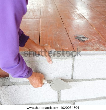 masonry worker make concrete wall by cement block and plaster at construction site #1020034804