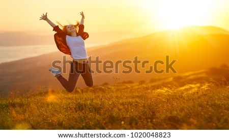 Happy woman jumping and enjoying life in field at sunset in mountains Royalty-Free Stock Photo #1020048823