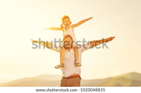 father's day. child daughter sits on her dad shoulders outdoors on a summer beach #1020048835