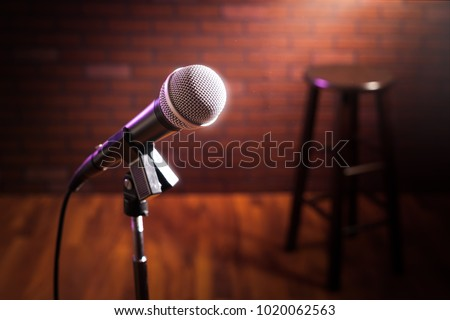 microphone on a stand up comedy stage with reflectors ray, high contrast image Royalty-Free Stock Photo #1020062563