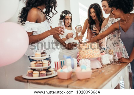 Group of female friends touching tummy of a pregnant woman at a baby shower. Female friends sharing love and support to pregnant woman. #1020093664