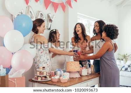 Women toasting with juices at baby shower party. Group of friends at baby shower party having juices. #1020093673