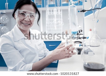 Positive attitude to work. Positive minded mature lady looking into the camera with a cheerful smile on her face while sitting in a laboratory and working with a lab glassware. #1020131827