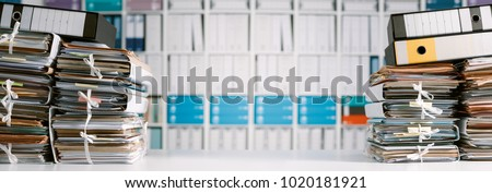 Stacks of files and paperwork in the office and bookshelves on the background: management and archive concept #1020181921