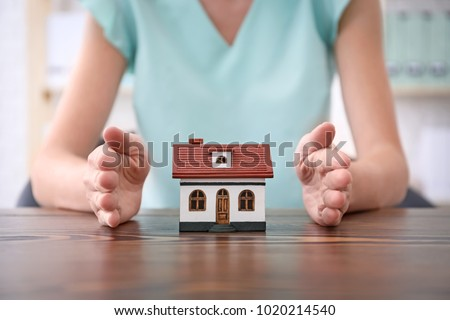 Real estate agent with house model at table. Insurance concept #1020214540