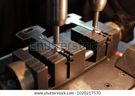 Locksmith in workshop makes new key. Professional making key in locksmith.  #1020217570
