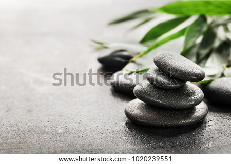 Stones for spa and green leaves on dark background. #1020239551
