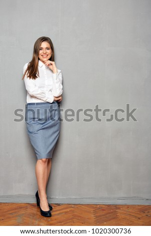 Smiling business woman standing against gray wall. Full body portrait. #1020300736