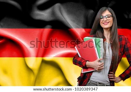 Happy female student holdimg books against national flag of Germany #1020389347