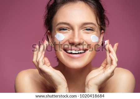 Laughing girl applying moisturizing cream on her face. Photo of young girl with flawless skin on pink background. Skin care and beauty concept #1020418684
