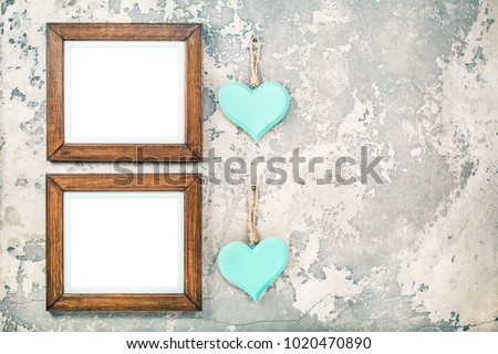 Two photo or picture frames blanks and pair of handmade Valentine's day love hearts hanging on vintage aged grunge textured concrete wall background. Retro old style filtered photo