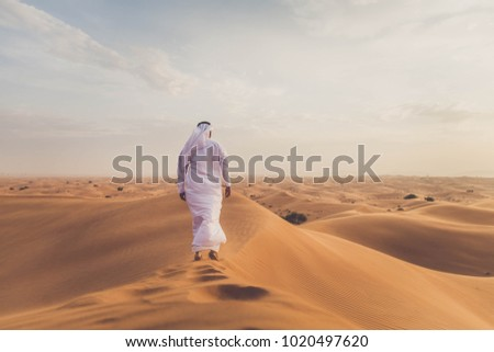 Arabian man walking  in the desert at sunrise #1020497620
