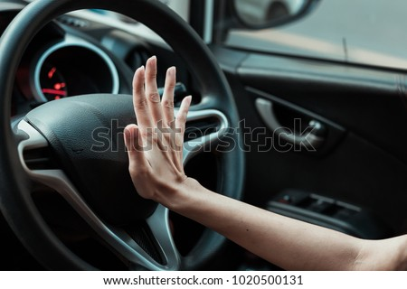 Hand pushing the horn button of the steering wheel inside the car with an anger. #1020500131
