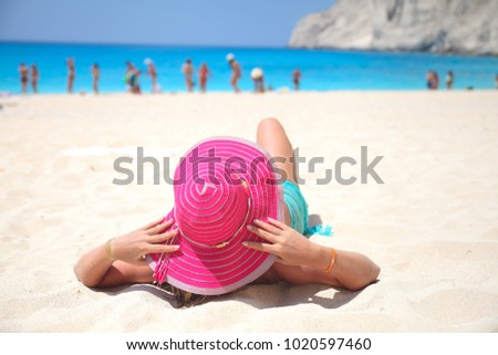 girl with a hat lying on the beach people in the background zakintos  #1020597460