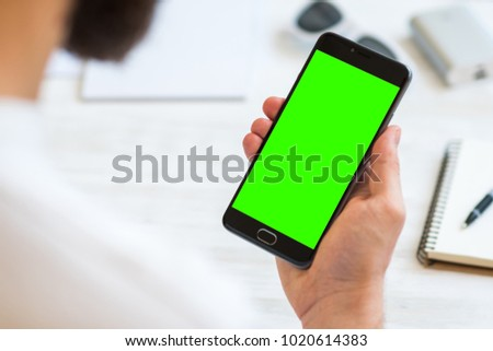 The man uses a smartphone with green screen for chroma key compositing. Concepts of using mobile devices, demos of the site in the mobile version comfort