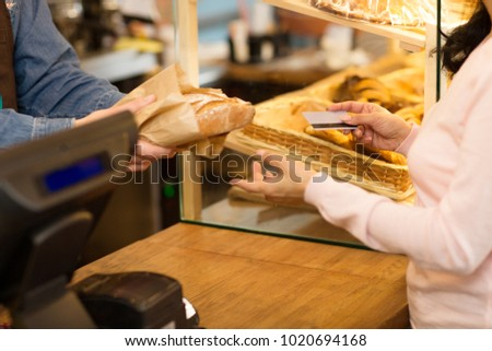 Cropped close up of a woman giving her credit card paying for fresh delicious bread shopping at the bakery store payment sales selling food consumerism banking modern lifestyle purchasing retail.