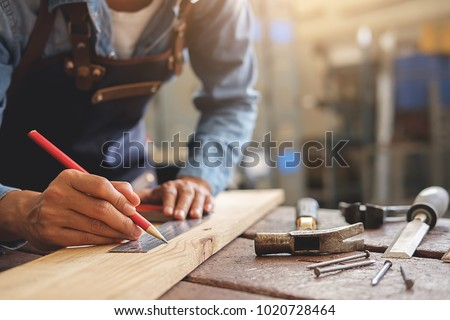 Carpenter working on woodworking machines in carpentry shop. woman works in a carpentry shop. #1020728464