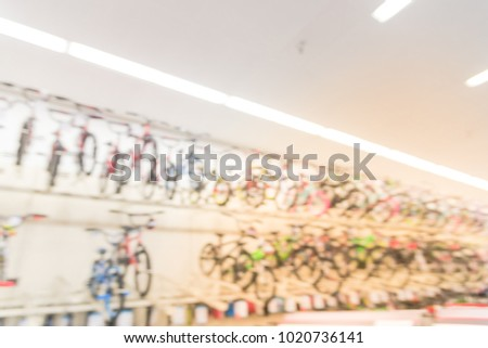 Blurred wide selection of bicycles at sporting goods chain store in Houston, Texas, USA. Various modern road, touring, cyclocross, mountain, commuter bikes on three tier sloping display rack #1020736141