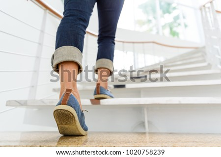 Young adult woman walking up the stairs with sun sport background. Royalty-Free Stock Photo #1020758239