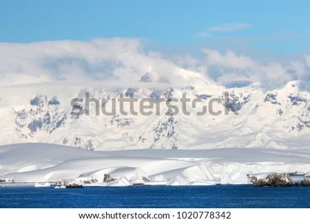 Antarctic ocean, Antarctica. Glacier Snow Covered Mountain. Dramatic blue Sky background #1020778342