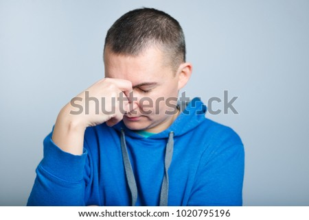 portrait of a man has the bad news and grabbed head, dressed in a blue hoodie, isolated on a gray background #1020795196