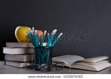 Books in stack apple and pencils in metal holder pot on wooden table in front of wall #1020876583