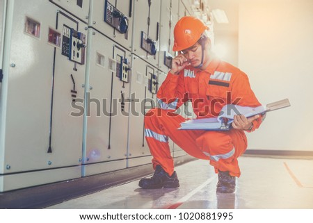 Electrical and instrument technician think and use manual guide to maintenance electric system at electric solar plant #1020881995
