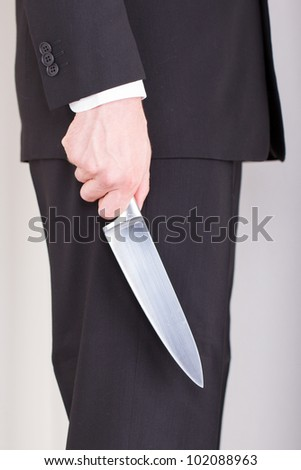 Man with knife, business suit, focus on the knife #102088963