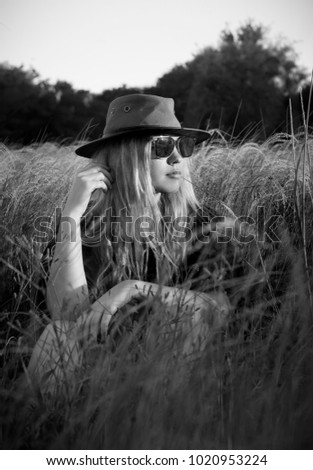 Black and white portrait of gorgeous blonde woman wearing sunglasses and hat, relaxing in a rural field of grass #1020953224