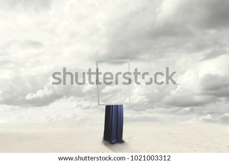 surreal moment of a woman hiding behind a picture of clouds equal to the landscape