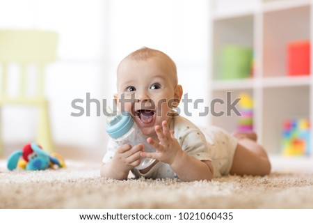 Cute baby boy drinking from bottle. Kid lying on carpet in nursery at home. Smiling child is 7 months old. Royalty-Free Stock Photo #1021060435