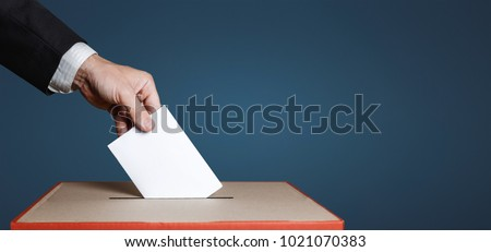 Voter Holds Envelope In Hand Above Vote Ballot On Blue Background. Freedom Democracy Concept #1021070383