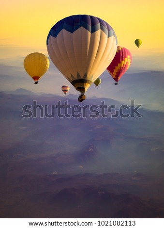 Multicolored Hot air balloons flying over serenity mountains peaks at sunrise. Travel concept with ballooning, golden sunlight and violet morning fog for vertical poster about adventures or dreams. #1021082113