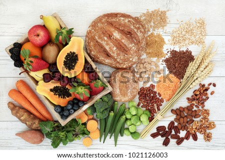 Healthy high fibre diet food concept with legumes, fruit, vegetables, wholegrain bread, cereals, grains, nuts and seeds. Super foods high in antioxidants, anthocyanins, omega 3 and vitamins. Top view. #1021126003