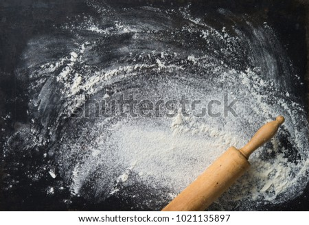 Baking background with the rolling pin and flour on dark table. Copy space for text  #1021135897