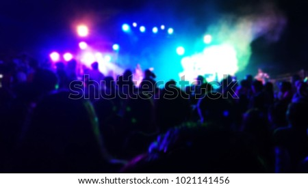 Abstract blur concert stage lights with crowd of people in front of the concert stage, colorful  concert  light background at the night,party with the the dark,technology for entertainment #1021141456