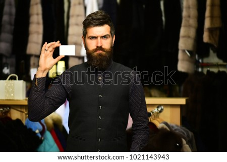 Customer with beard and business card. Shop assistant with empty paper. Finance and shopping concept. Man with strict face holds card on furry coats racks background, defocused #1021143943