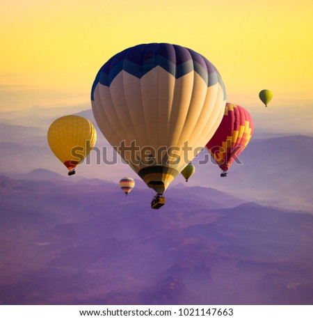 Hot air balloons above ultraviolet mountain hills in golden sunlight. Sunrise with flying air baskets for your stories about travel dreams, active leisure or holidays concept. #1021147663